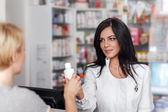 Pharmacist selling medicine in drugstore — Foto Stock