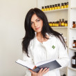 Brunette pharmacist reading book — Stock Photo