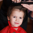 Young child with smile at the hairdresser having a haircut — Stock Photo
