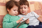 Little boys playing on tablet at home — Stock Photo