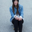 Stock Photo: Young brunette skateboarder girl sitting on skateboard