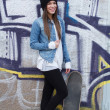 Stock Photo: Young fashionable happy brunette skateboarder girl