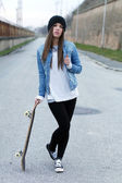 Teenager posing with skateboard — Stockfoto
