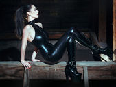 Sexy dominatrix at night posing on timber — Stock Photo