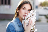 Beautiful young woman smelling cherry blossom — Stock Photo