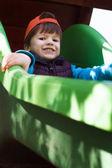 Little boy in orange cap on slide — Stock Photo
