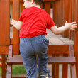 Cute little boy climbing up on ladder — Stock Photo #45271311