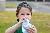 Little boy in cap drink water — Stock Photo