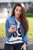 Mujer joven holding smartphone — Foto de Stock