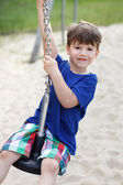 Little preschooler boy sitting on wire rope swing — Foto de Stock