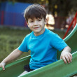Little caucasian boy smiling on slide — Stock Photo