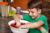 Six year old caucasian boy eating cherry — Stock Photo