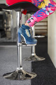 Woman sitting on bar stool in high heel ankle boots — Stock Photo