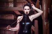 Sexy woman in catsuit with whip — Stok fotoğraf