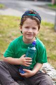 Liten pojke sitta med flaska vatten — Stockfoto