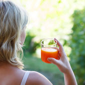 Blonde woman holding juice — Stock fotografie