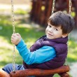 Little boy in winter waistcoat swinging — Stock Photo #49520423