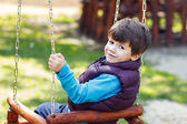 Little boy in winter waistcoat swinging — Stock Photo