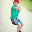 Little boy in red cap sit on swing rope — Stock Photo #49577923