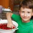 Boy take out fresh cherry from bowl — Stock Photo #49578275