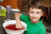 Boy take out fresh cherry from bowl — Stock Photo