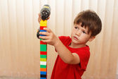 Little boy build tower from blocks — Stock Photo