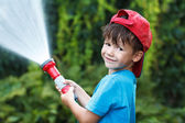 Boy in cap pours water outdoor — Stock Photo