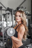 Fitness model pumping up muscles — Stock Photo