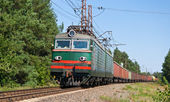 Freight train hauled by electric locomotive — Stok fotoğraf