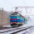 Passenger train rapidly moving along the snow track - Stock Photo