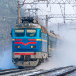 Passenger train rapidly moving along the snowy track - Stock Photo