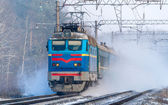 Passenger train rapidly moving along the snowy track — Stock Photo