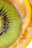Tropical fruits in water, macro view — Stock Photo