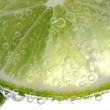 Stock Photo: Macro view of lime slices with bubbles