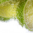 Bubbles of mineral water and sliced lime — Stock Photo
