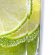 Stock Photo: Macro view of sliced lime in glass of water