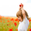 Girl on meadow with a red poppies — Stock Photo