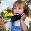Adorable baby play with cell phone calling sitting in deep grass in park — Stock Photo #12054823