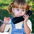 Adorable baby play with cell phone calling sitting in deep grass in park — Stock Photo #12054830