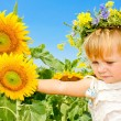 Beautiful little girl and sunflowers — Stock Photo
