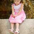 Beautiful little baby girl sitting on bench in summer garden — Foto Stock
