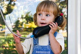 Adorable baby play with cell phone calling sitting in deep grass in park — Stock Photo