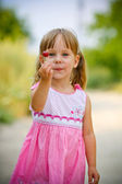 Beautiful little girl holding cherries in hand and ready to ea — Stock Photo