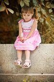 Beautiful little baby girl sitting on bench in summer garden — Stock Photo