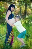 Cute boy kissing his mothers pregnant belly — Stock Photo