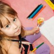 Small beautiful girl paints on apaper on floor — Stock Photo