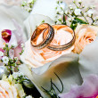 Gold wedding rings on a bouquet of white roses — Stock Photo