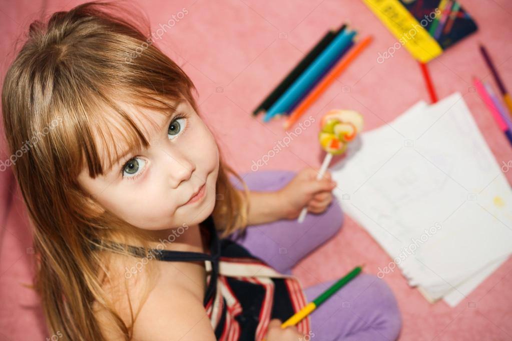 	small beautiful girl paints on apaper on floor  Stock Photo #12127988