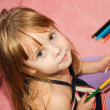Small beautiful girl paints on apaper on floor — Stock Photo #12146497