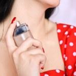 Young woman spraying perfume on neck — Stock Photo